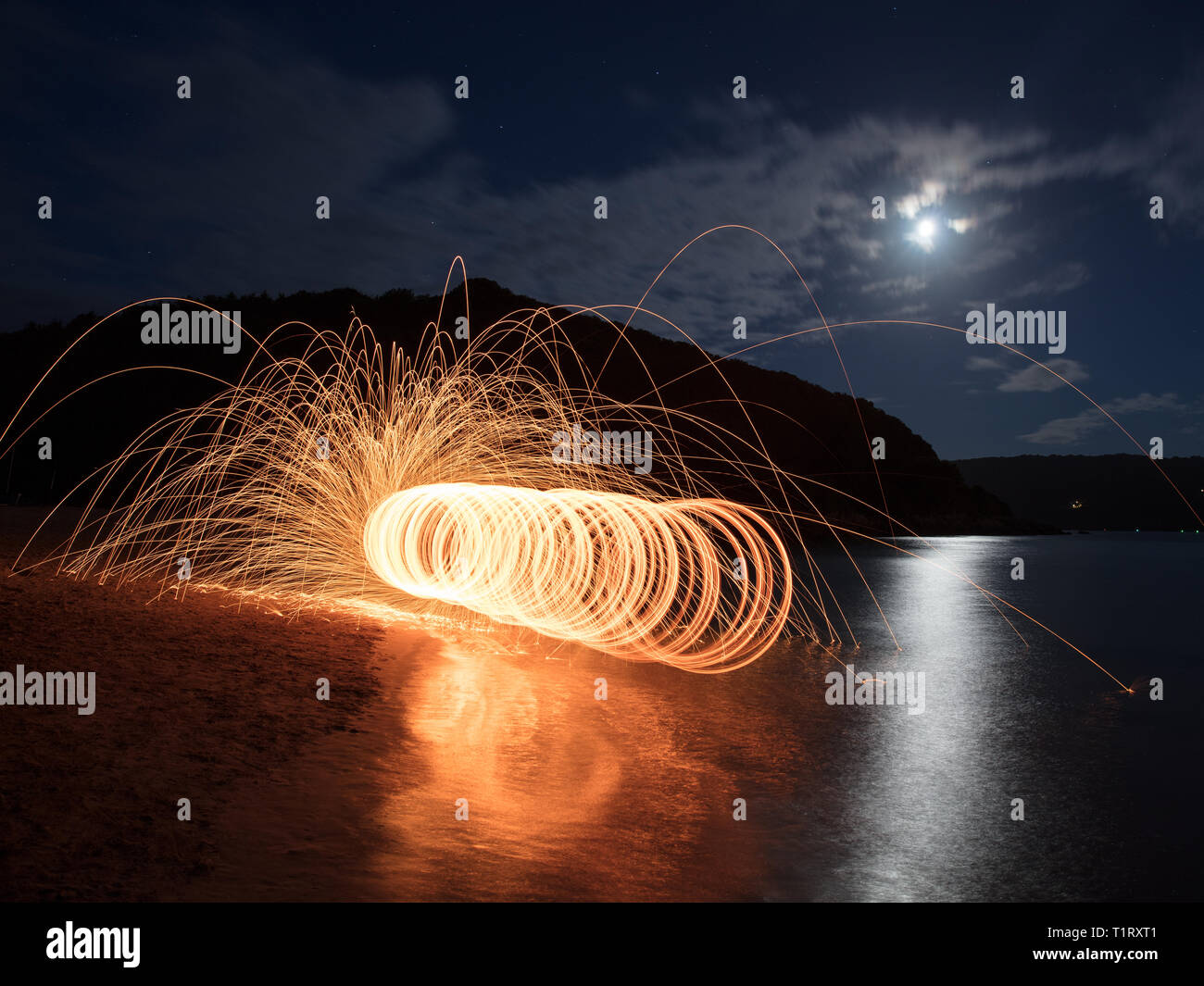A steel wool shot on East Portlemouth beach in Devon. Steel wool photography involves using a whisk,steel wool and a dog lead. Stock Photo