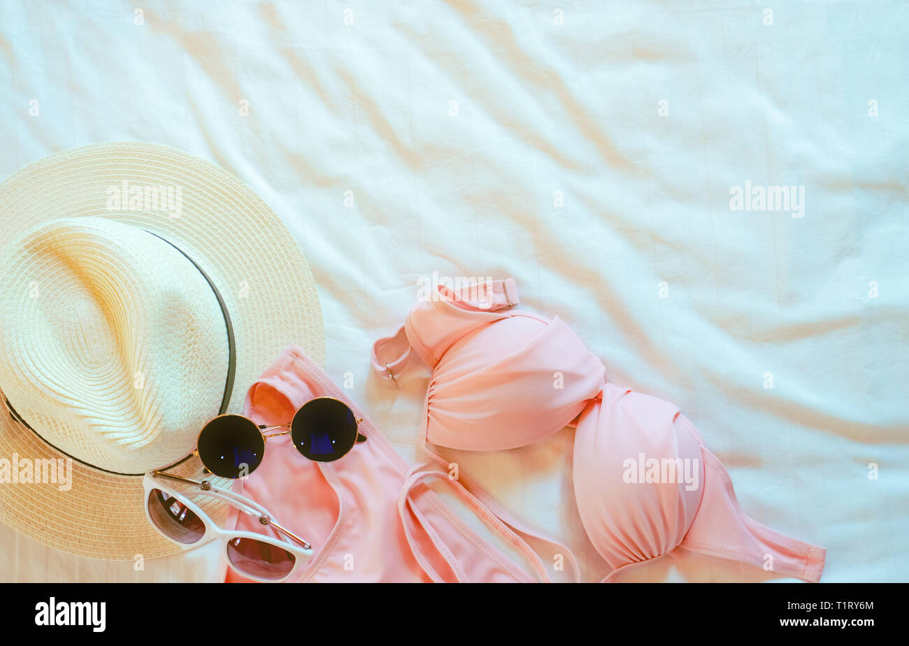 6c5c6027 Top view of bikini swimsuit, sunglasses, and straw hat on bed sheet. Woman's