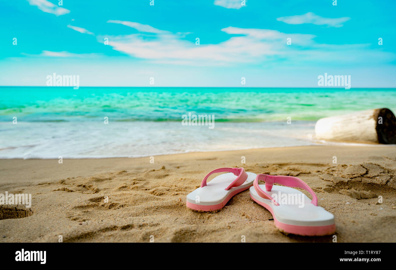 Pink and white sandals on sand beach. Casual style flip-flop were removed at seaside. Summer vacation on tropical beach. Fun holiday travel on sandy - Stock Image