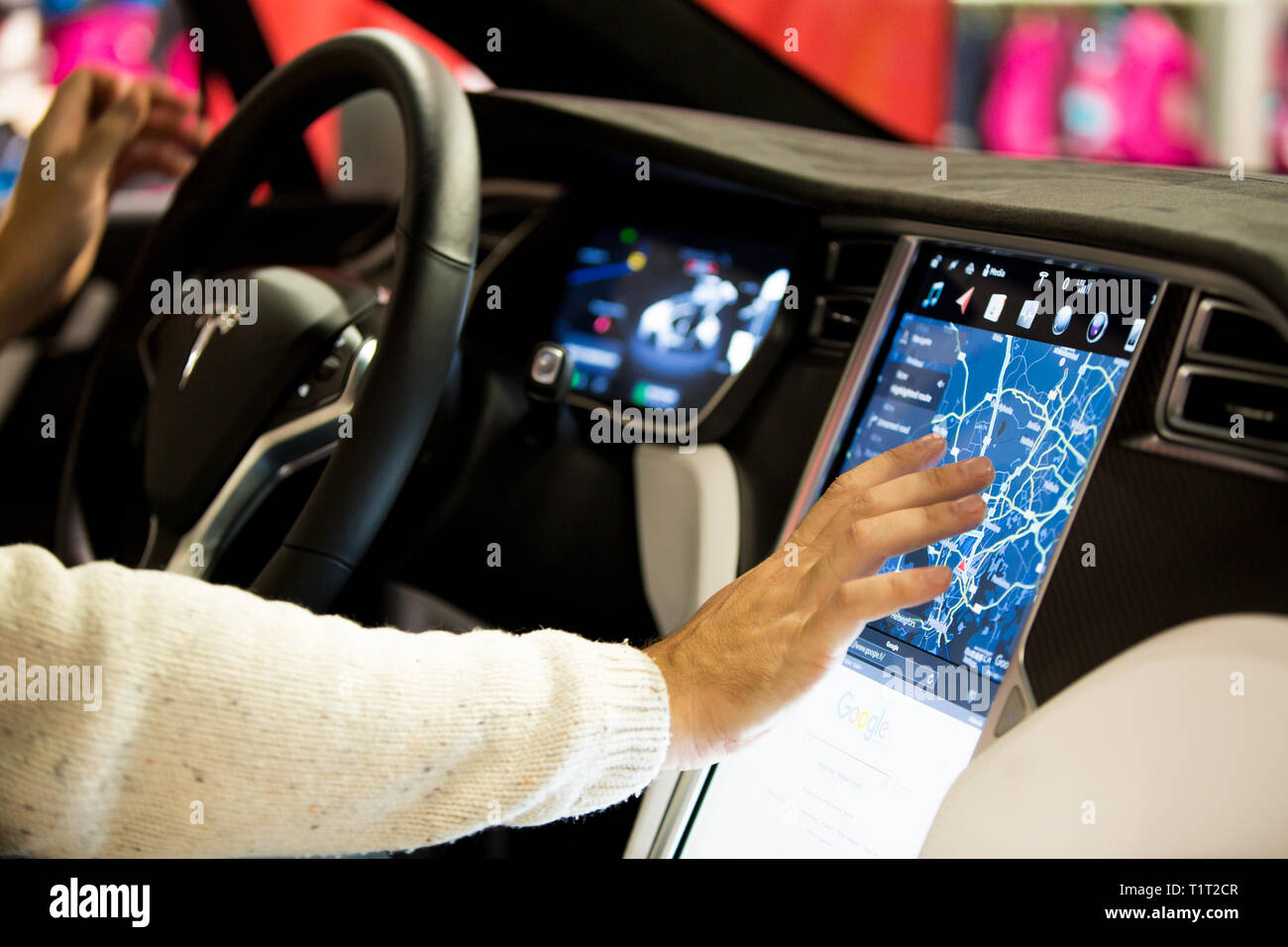 HELSINKI, FINLAND - NOVEMBER 04, 2016: The interior of a Tesla Model X electric car with large touch screen dashboard.  Hand using gps navigation - Stock Image
