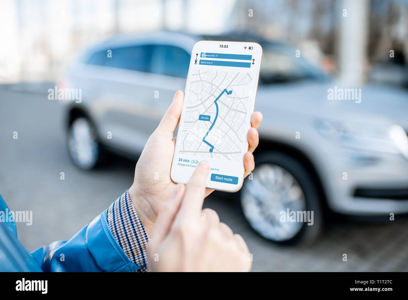 Woman using smart phone with navigation app, close-up view with modern car on the background - Stock Image