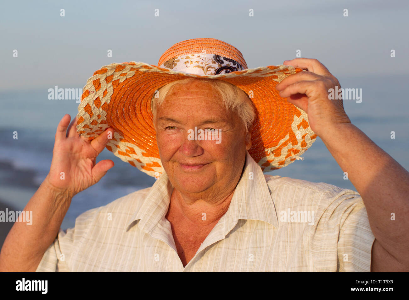 Beautiful elderly woman in a hat on the background of the sea. Face of an old woman with a smile. Grandma on vacation - Stock Image