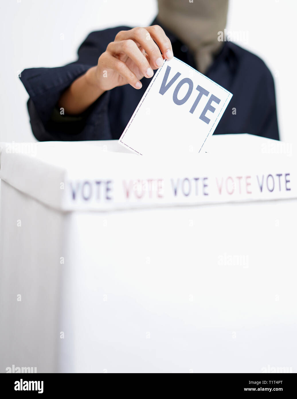 The hand putting a ballot in the ballot box. - Stock Image