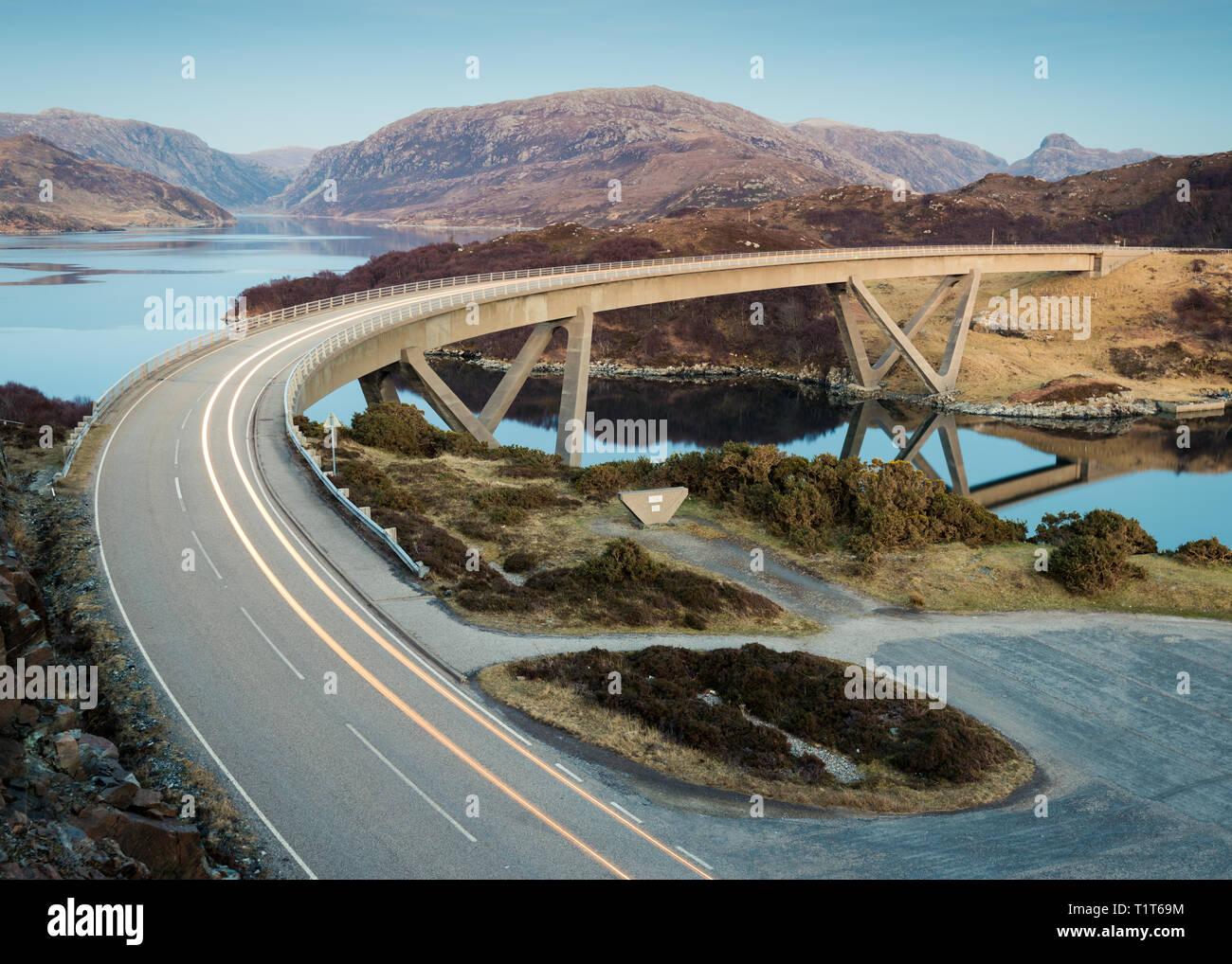 The Kylesku Bridge crossing at sunset with car tail light streaks along the road, Assynt, Scottish Highlands, UK - Stock Image