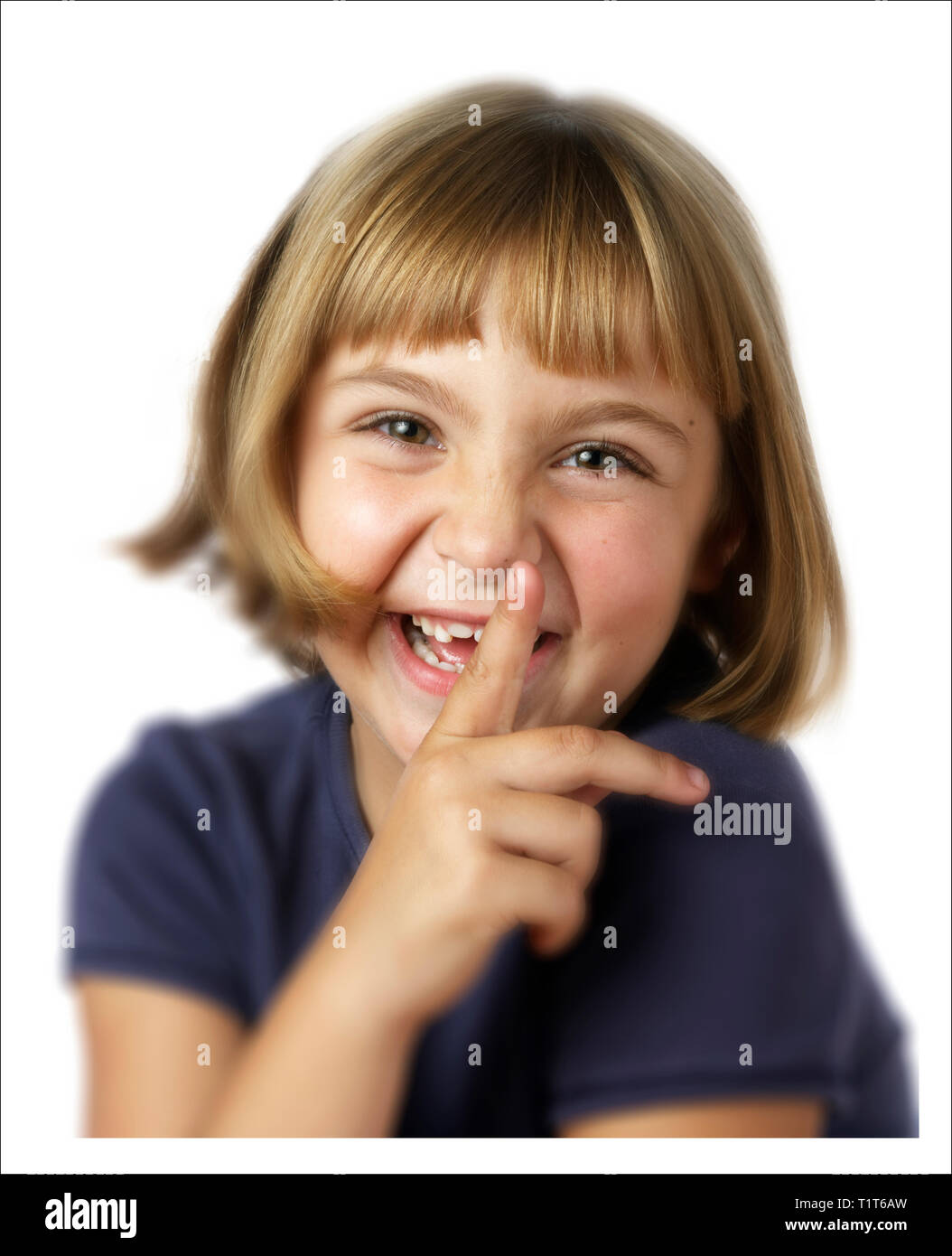Cute blonde seven-year-old girl with finger to her lips - Stock Image