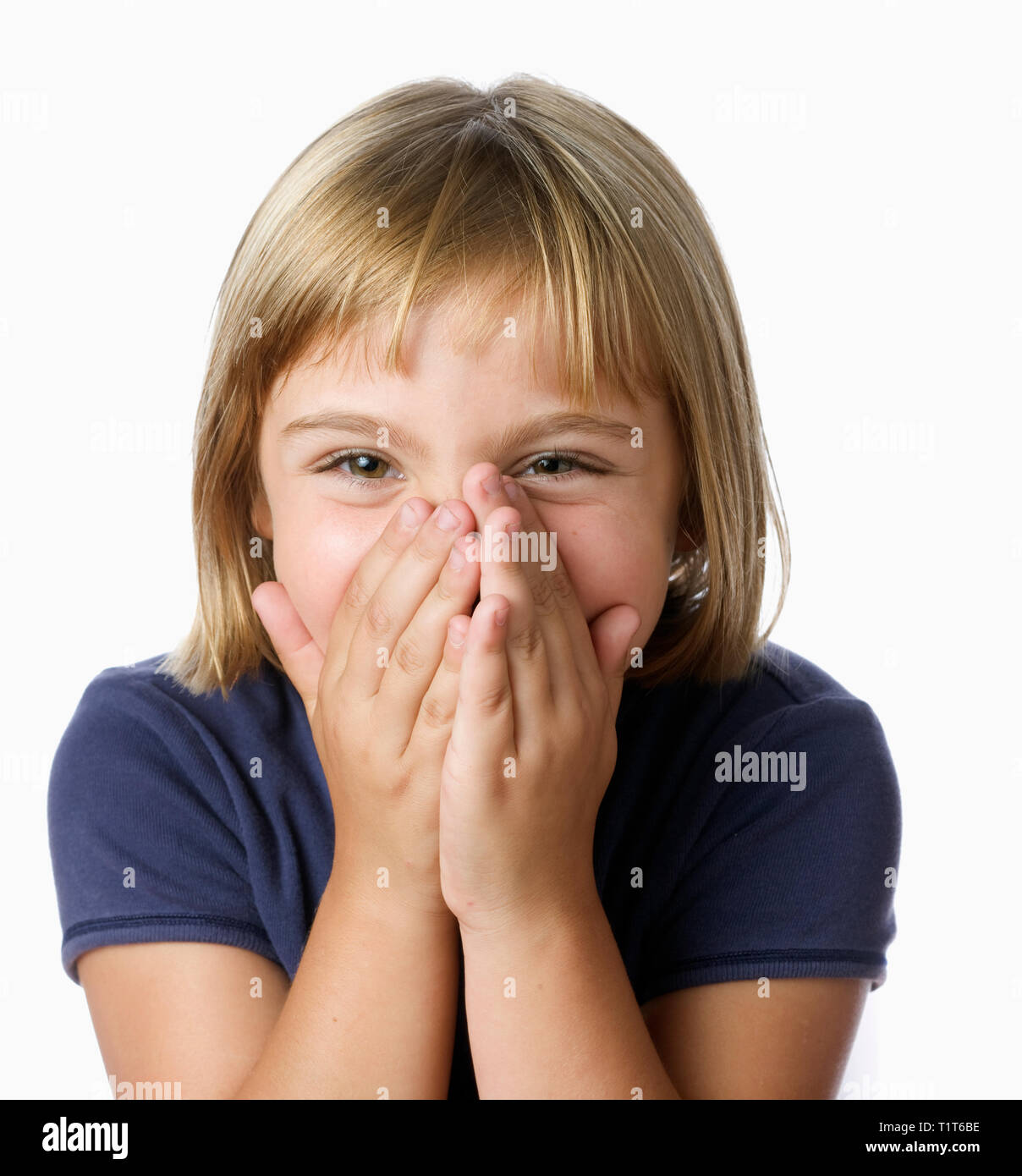 Blonde 7 year-old girl laughing with hands over mouth - Stock Image