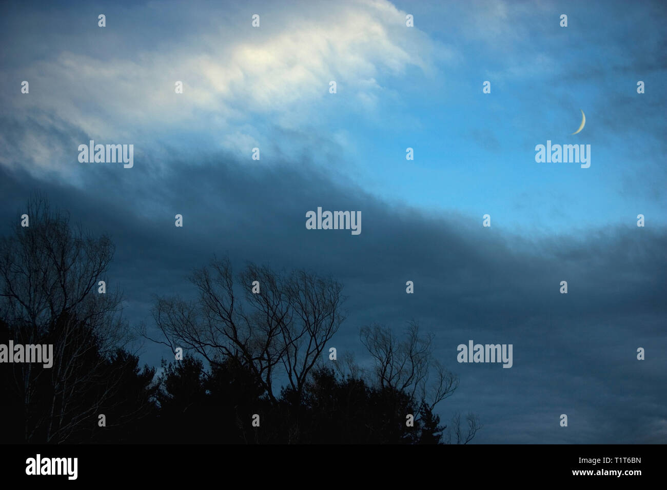 Storm clouds clear as an approaching front moves out, showing the new moon - Stock Image