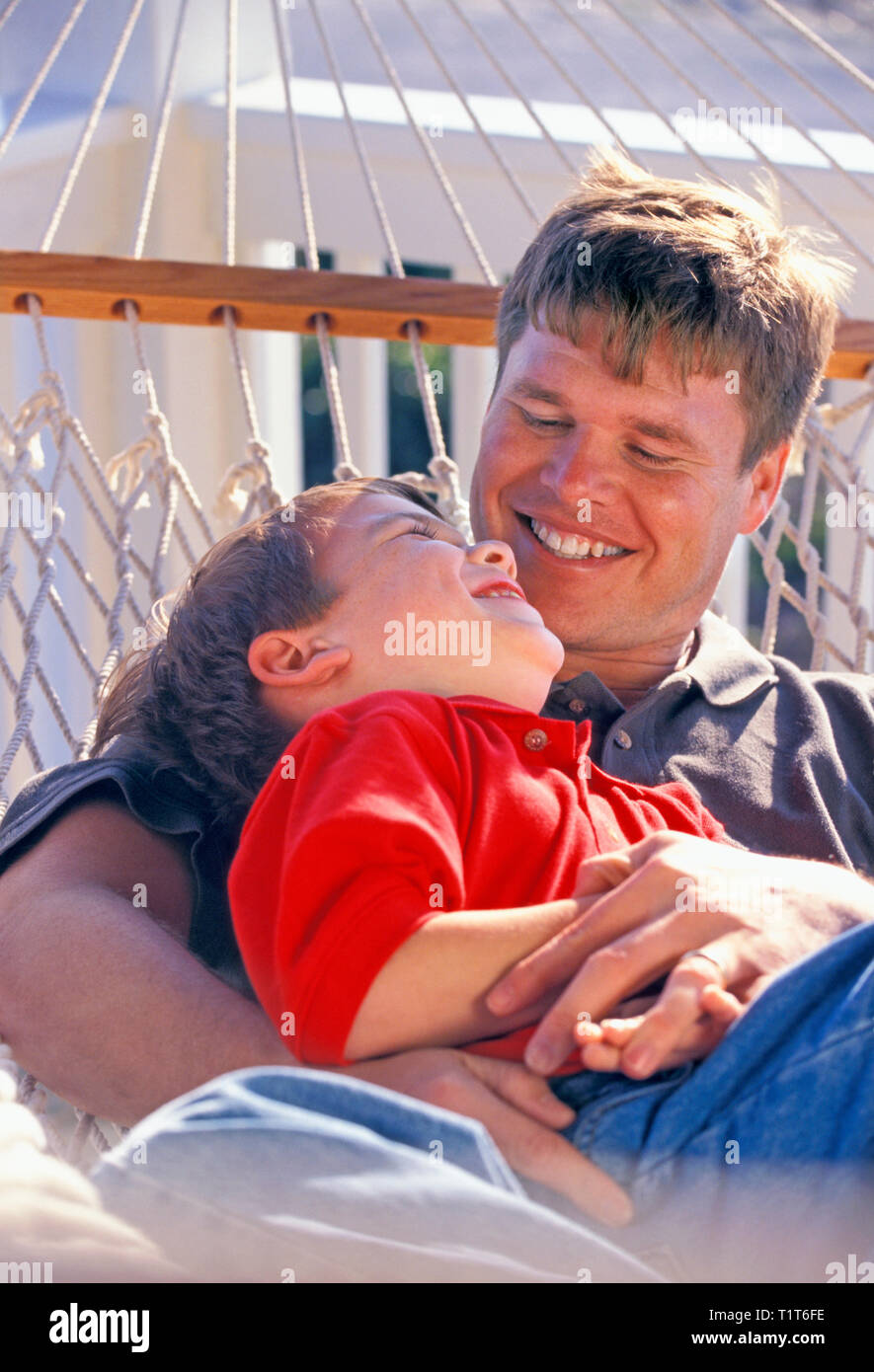 Father and son relax in a hammock - Stock Image