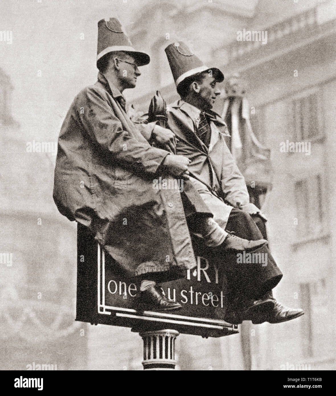 Two men atop a traffic sign in order to get a better view of the Coronation procession of George VI and Queen Elizabeth, London, England, 1937.  From The Coronation in Pictures, published 1937. - Stock Image