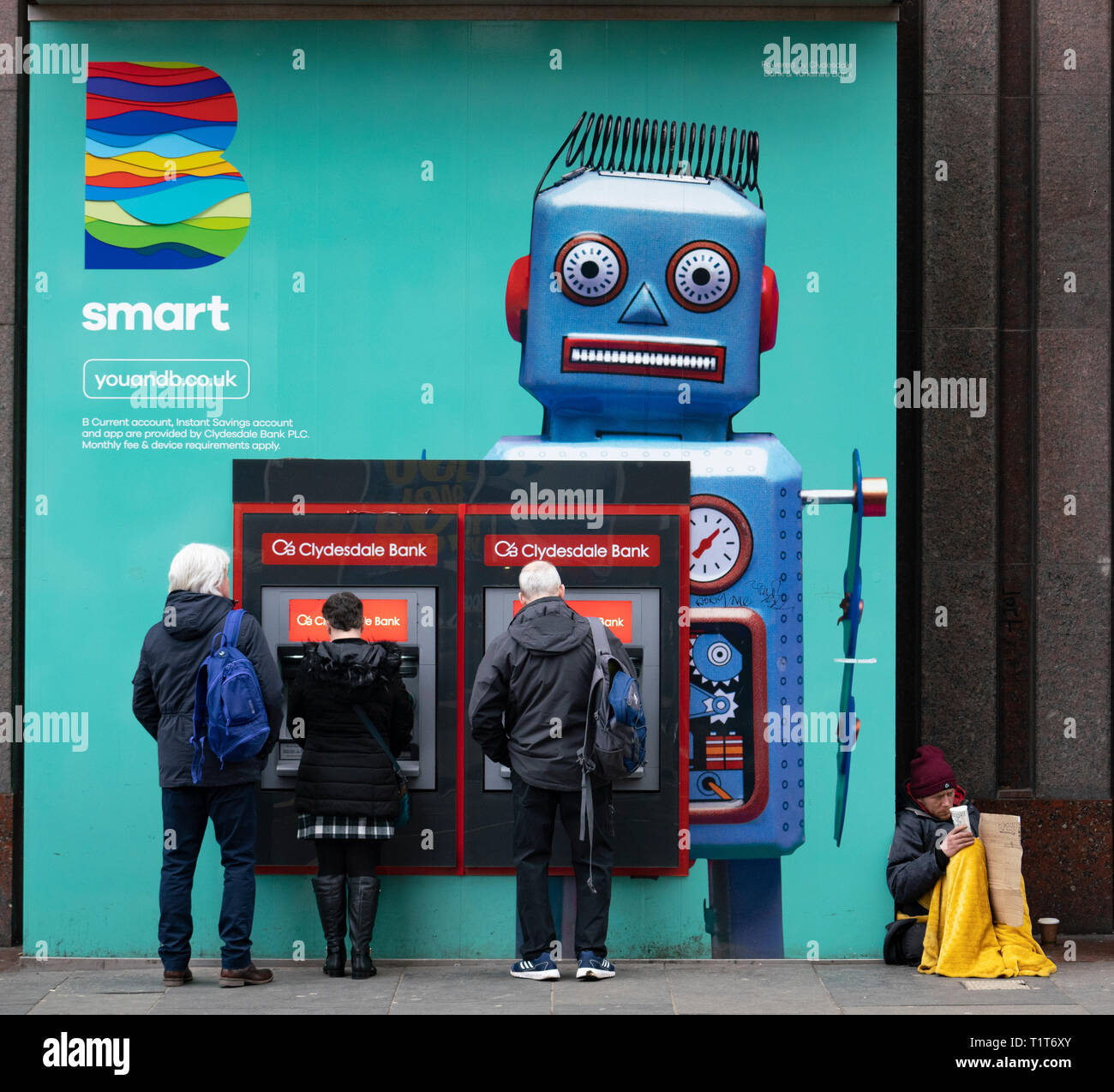 People using ATM machine next to homeless person in central Glasgow, Scotland UK - Stock Image