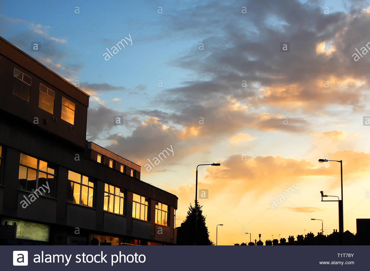 The sun sets over some London offices, with warm tones reflected in the building's windows. - Stock Image