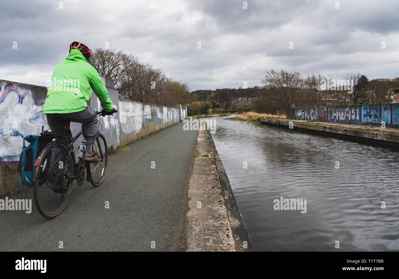 Cyclist on the towpath of the Union Canal in early spring  in Edinburgh, Scotland, UK - Stock Image
