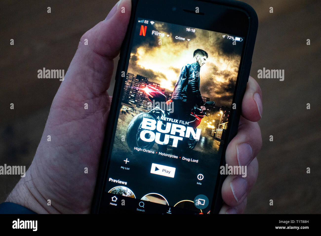 Using a mobile phone to browse Netflix movie streaming app Stock
