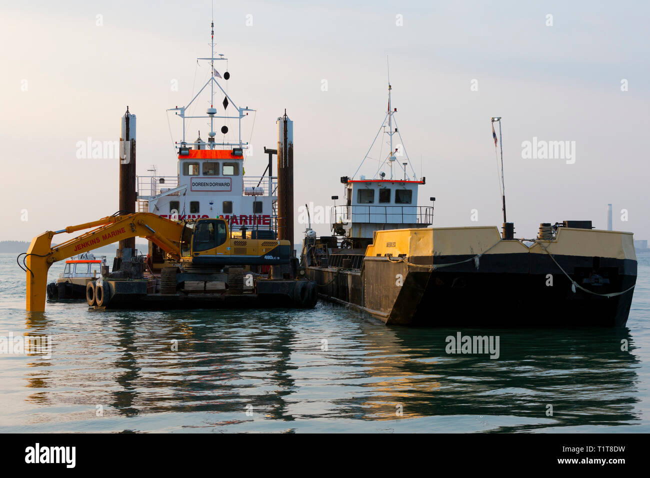 dredging,dredger,hopper,barge,harbour,harbor,JCB,digger,mud,gravel,increasing,depth,channel,waterway,sea,silted,up,silt,grab,Cowes,Isle of Wight, - Stock Image