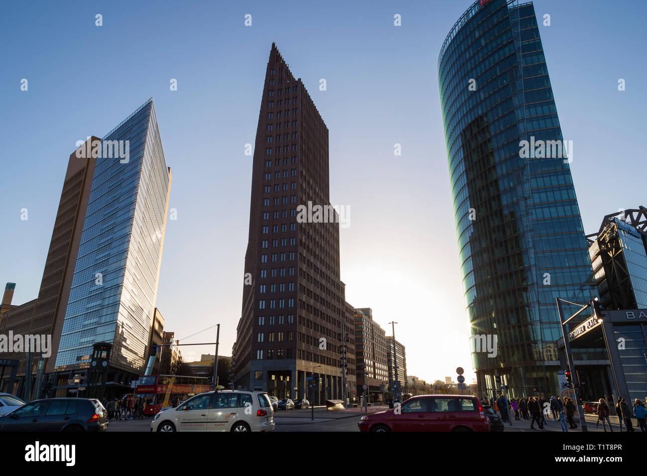 Modern high-rise buildings against clear blue sky and people and cars on the streets at Potsdamer Platz in downtown Berlin, Germany, on a sunny day. Stock Photo