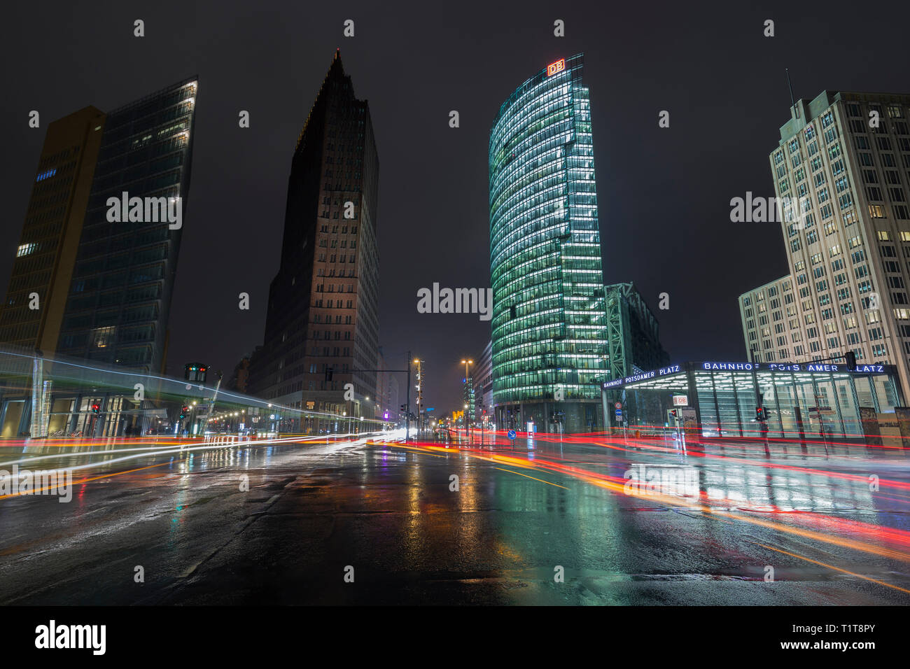 Lit modern high-rise buildings, cars' light trails, wet roads and entrance to train station at Potsdamer Platz in downtown Berlin, Germany, at dusk. Stock Photo