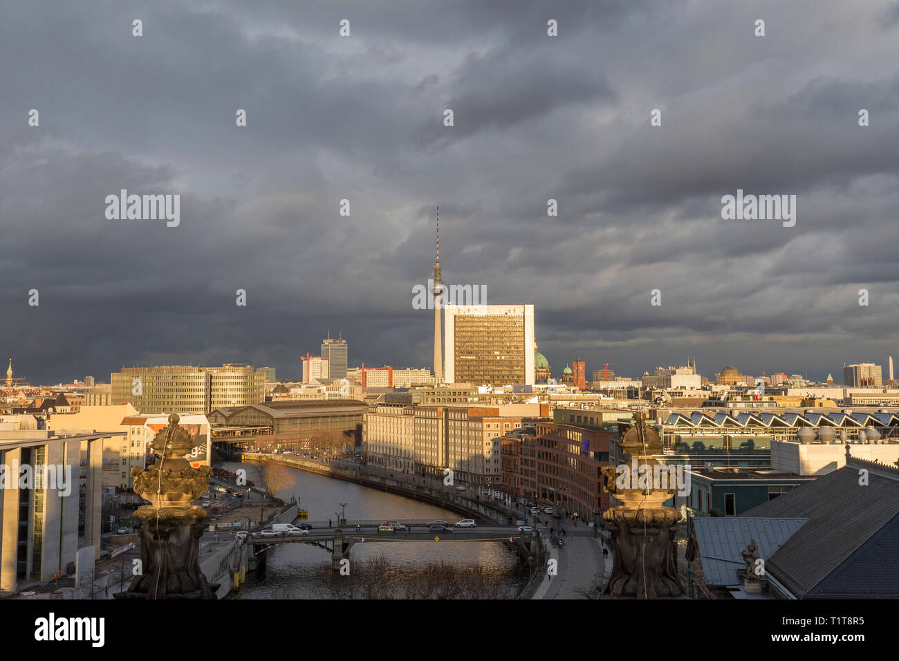 View of the Spree River, Fernsehturm TV Tower and buildings at the downtown Berlin, Germany, on a sunny day. Dark clouds. Copy space. Stock Photo