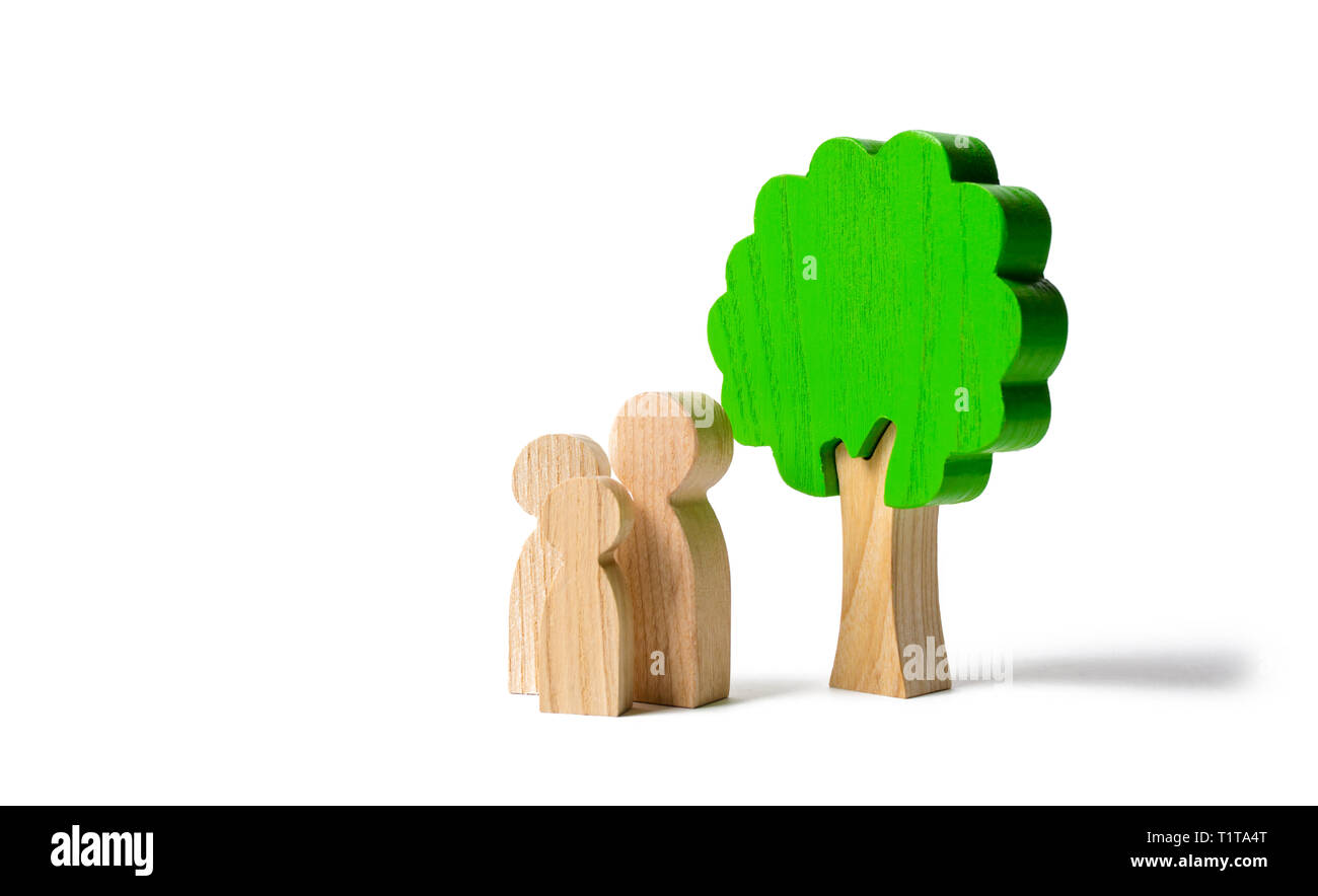 Family figures are standing near the tree on an isolated background. Pastime with family, kinship and parenting. Instilling good qualities and values  - Stock Image
