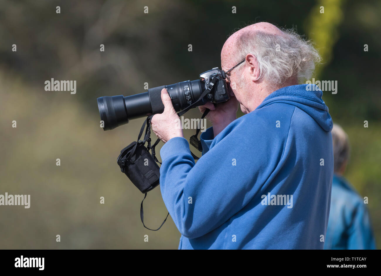 Senior man taking photographs with a DSLR and long telephoto lens. Side view of male taking photos with a digital camera. Pensioner hobby. - Stock Image
