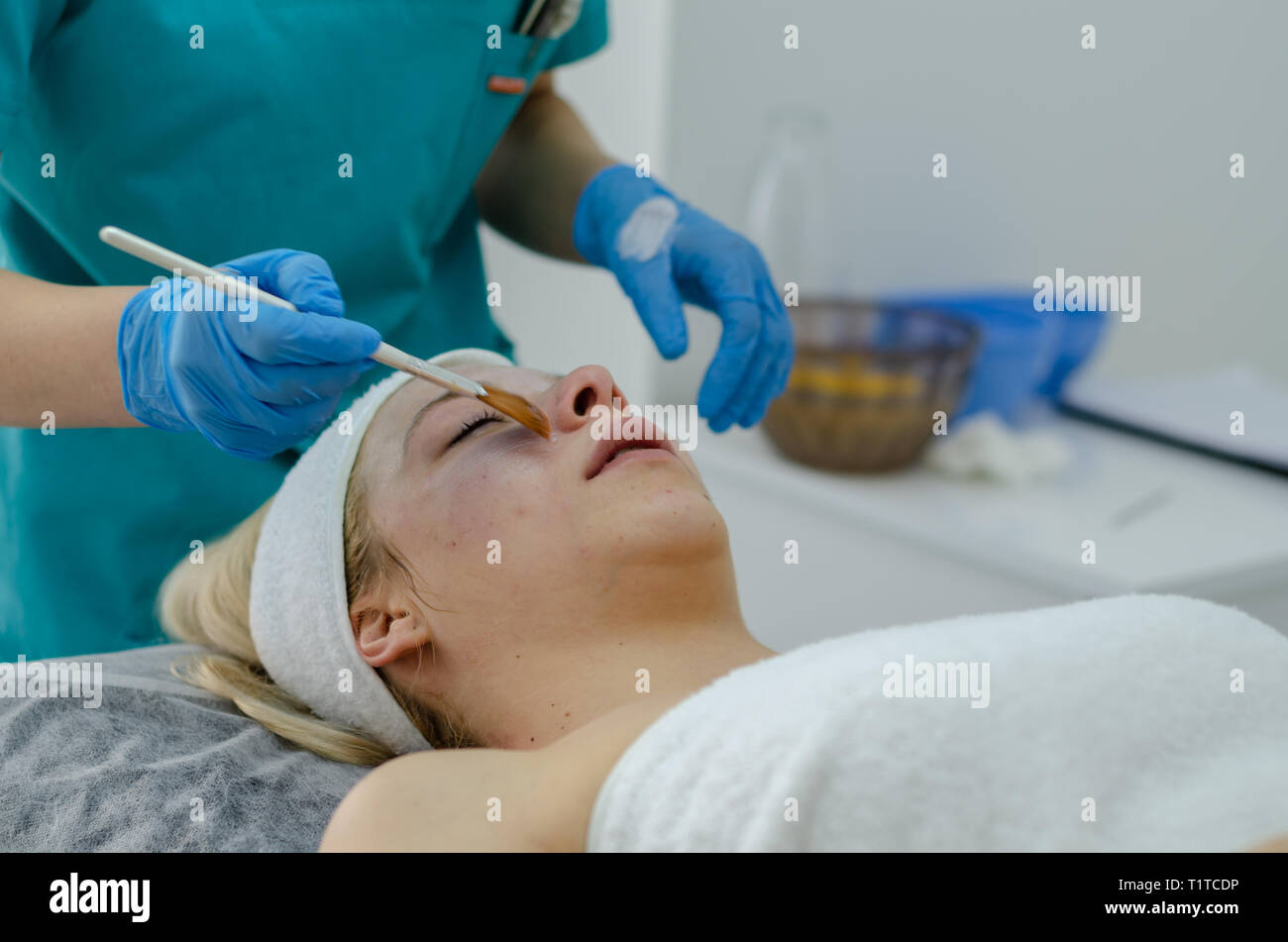 Beautiful woman having a facial cosmetic scrub treatment. Esthetician is cleaning blackheads. Anti-aging, facial skin care and luxury lifestyle concep - Stock Image