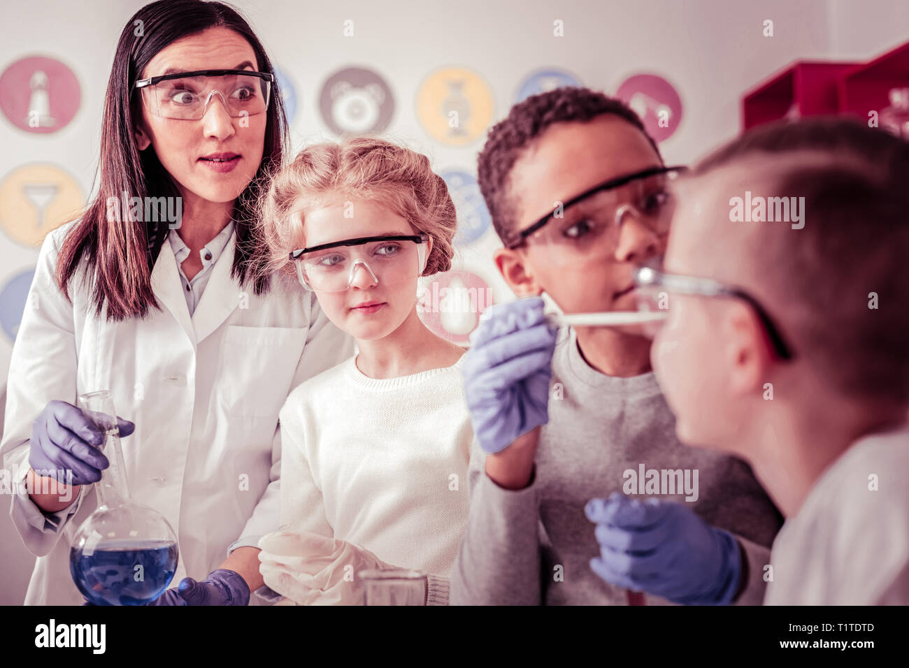 Elementary school group looking surprised on their classmate - Stock Image