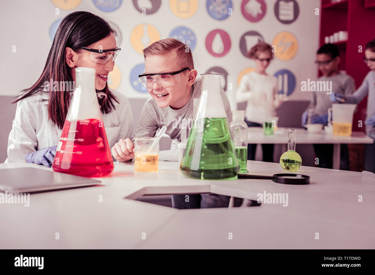 Beaming teacher explaining her interested schoolkid aspects - Stock Image