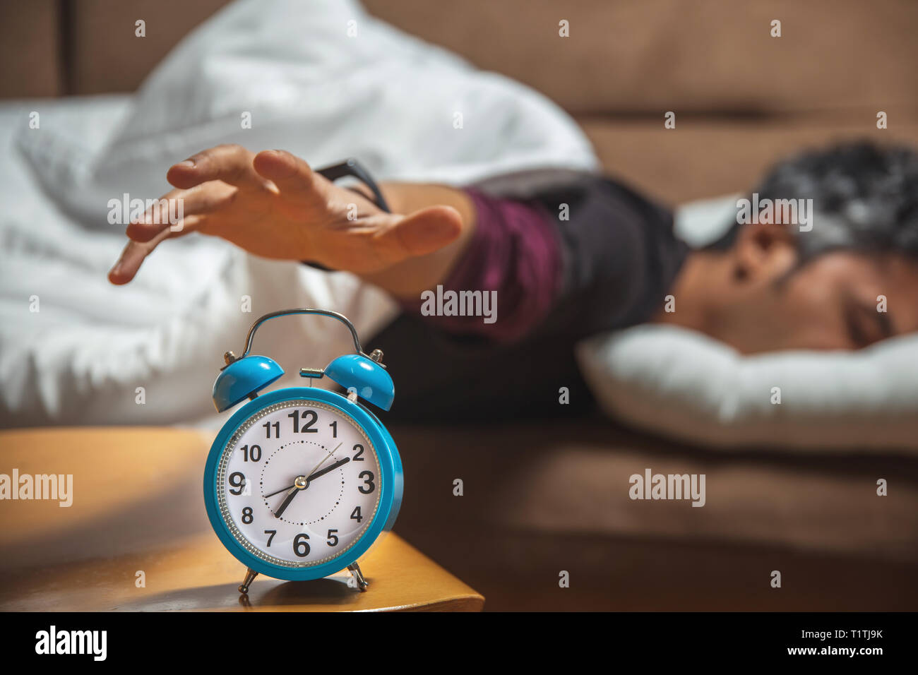 close up view of a sleepy guy trying to snooze a vintage clock - Stock Image