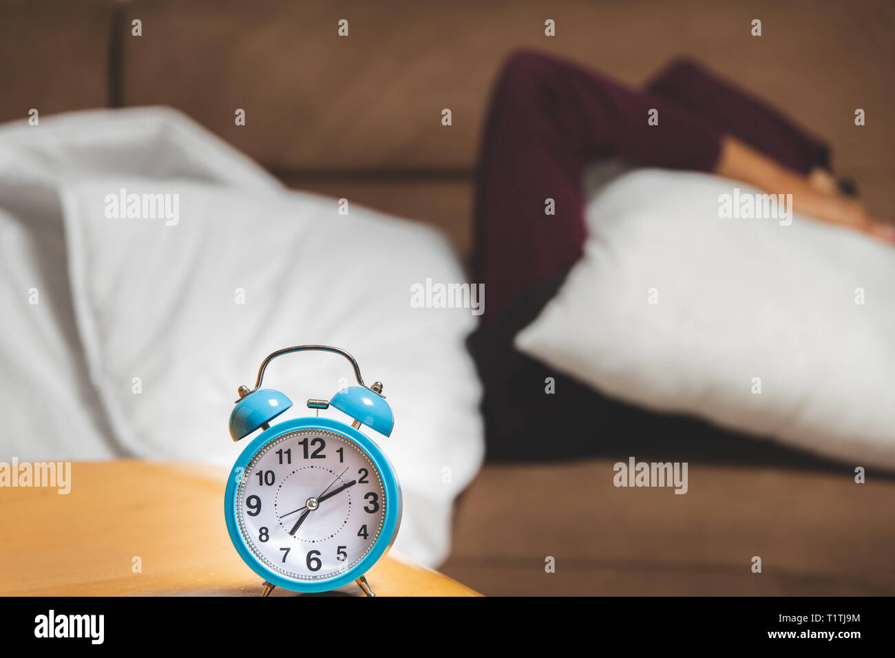 close up view of a guy trying to sleep hiding under a pillow - Stock Image
