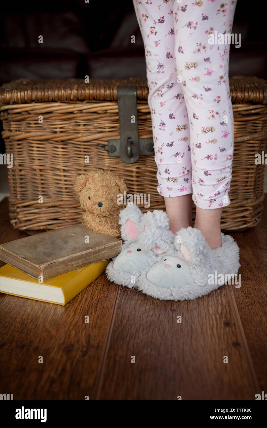 Child in pyjamas standing next to books and teddy on a wooden floor Stock Photo