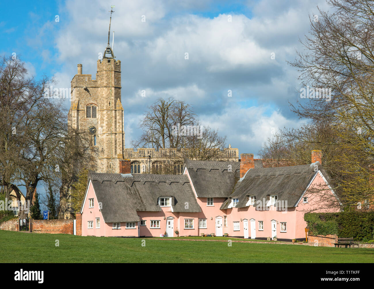 Thatched cottage painted in Suffolk pink with St. Mary the Virgin's Church on the village green. Cavendish, Suffolk, East Anglia, UK. - Stock Image