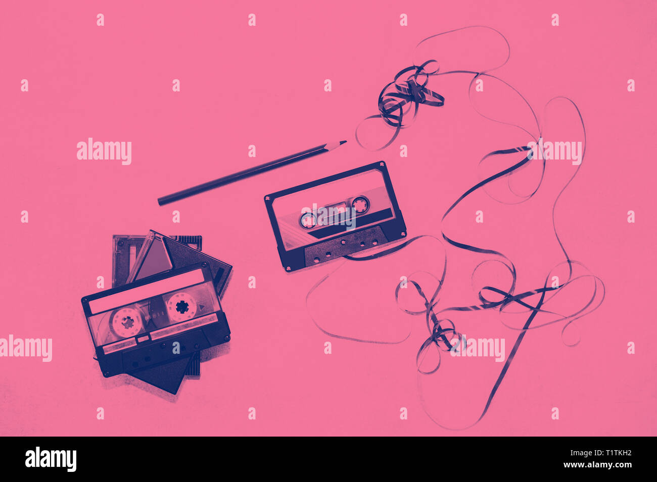 Cassette tape over white background with tangled ribbon. - Stock Image