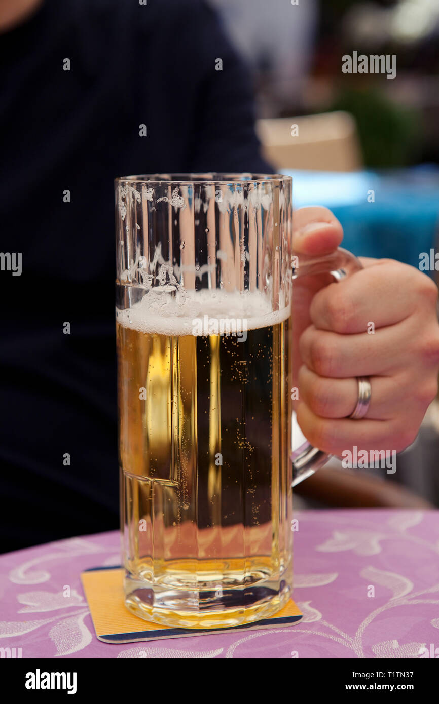 Man holding glass tankard of German beer on a table at a street cafe Stock Photo
