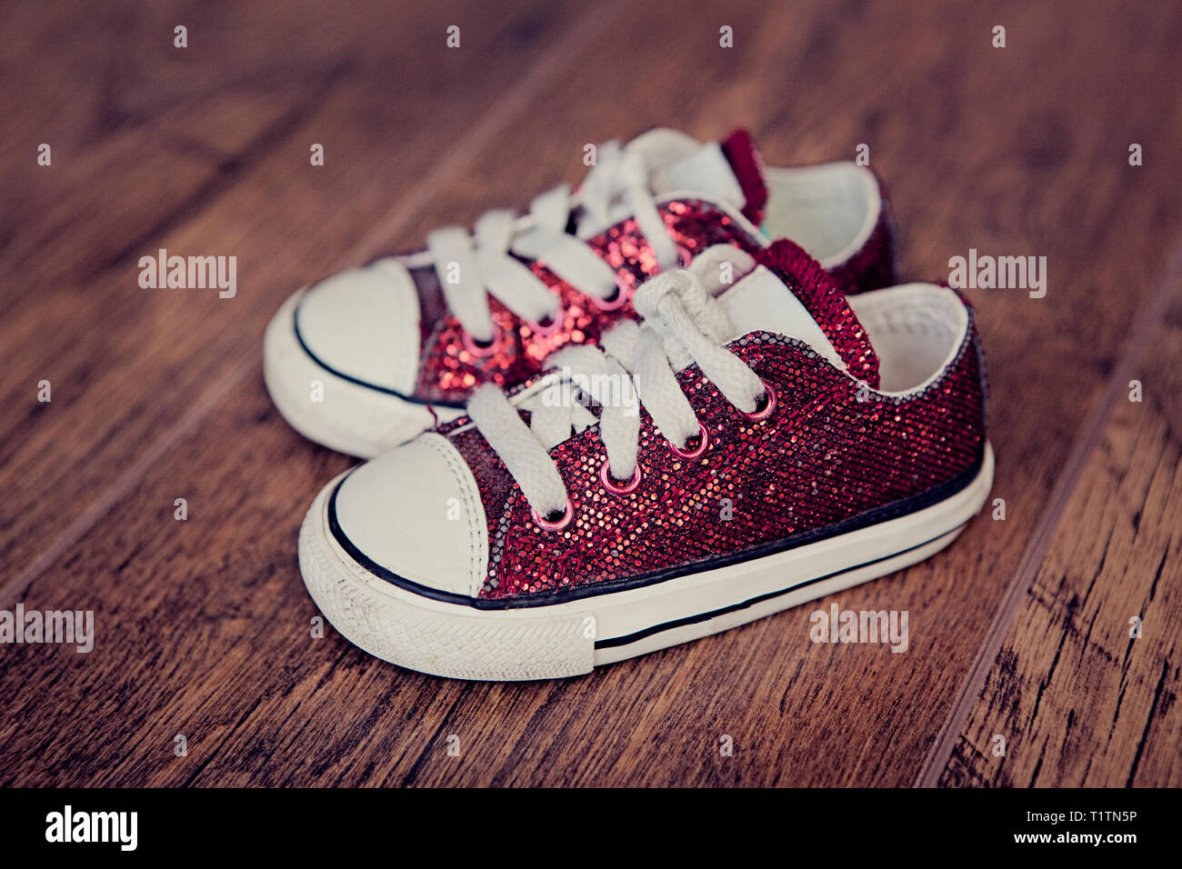 Small red baby sneakers with shoelaces on a wooden floor - Stock Image
