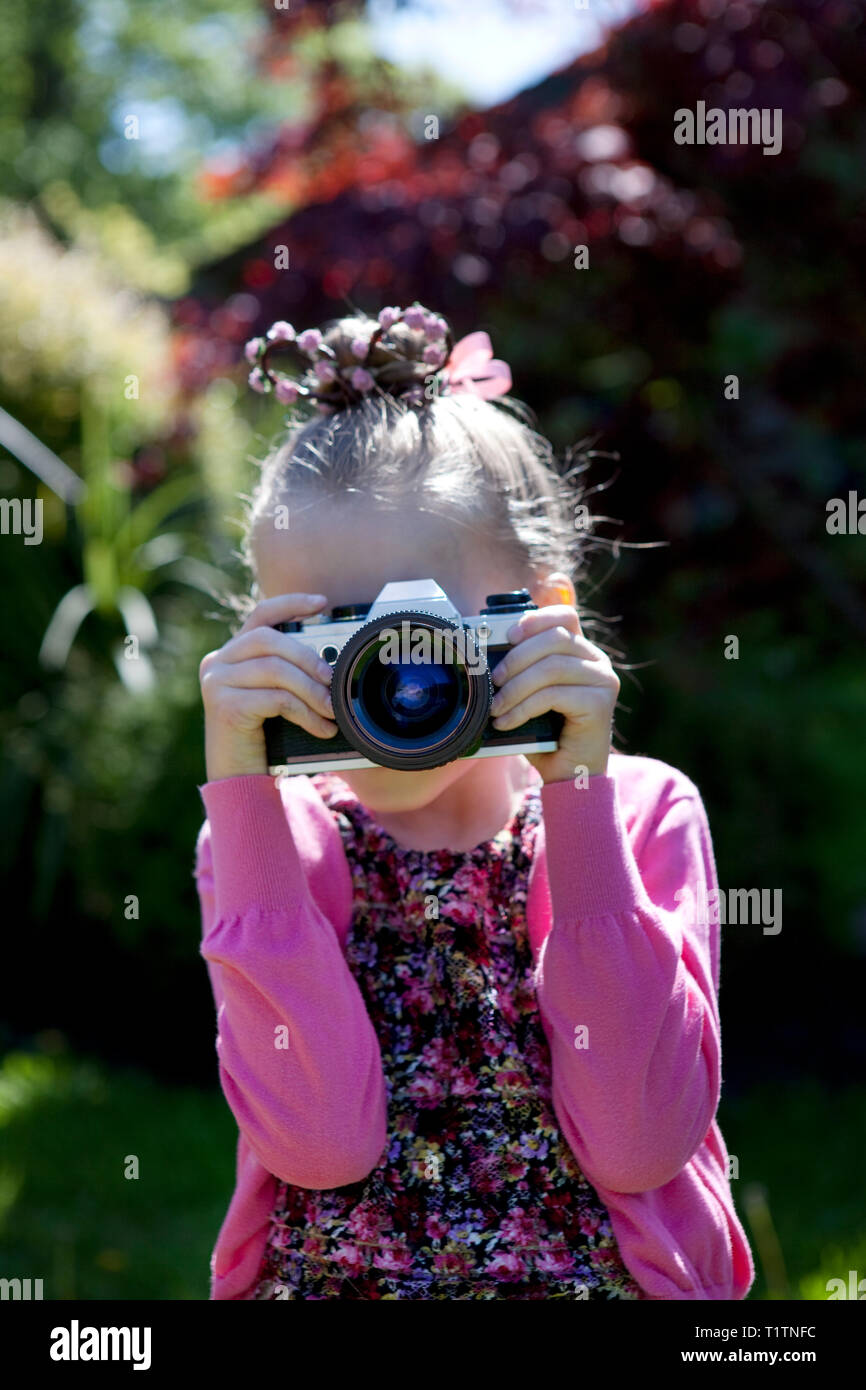 Child using an old SLR film camera to take a photograph - Stock Image