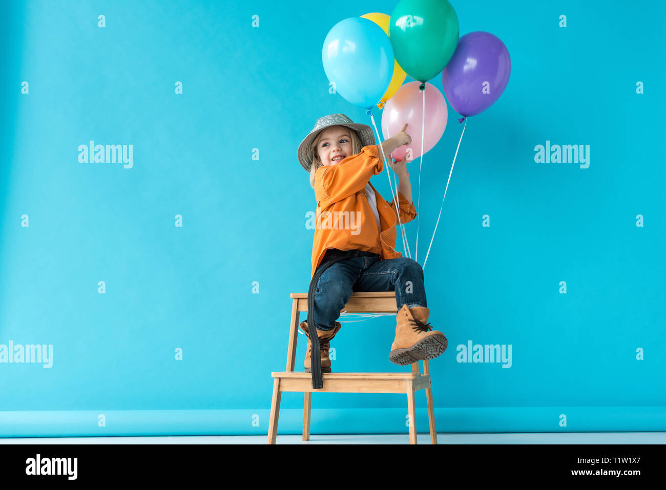 cute kid in jeans and orange shirt sitting on stairs and pointing with finger at balloons Stock Photo