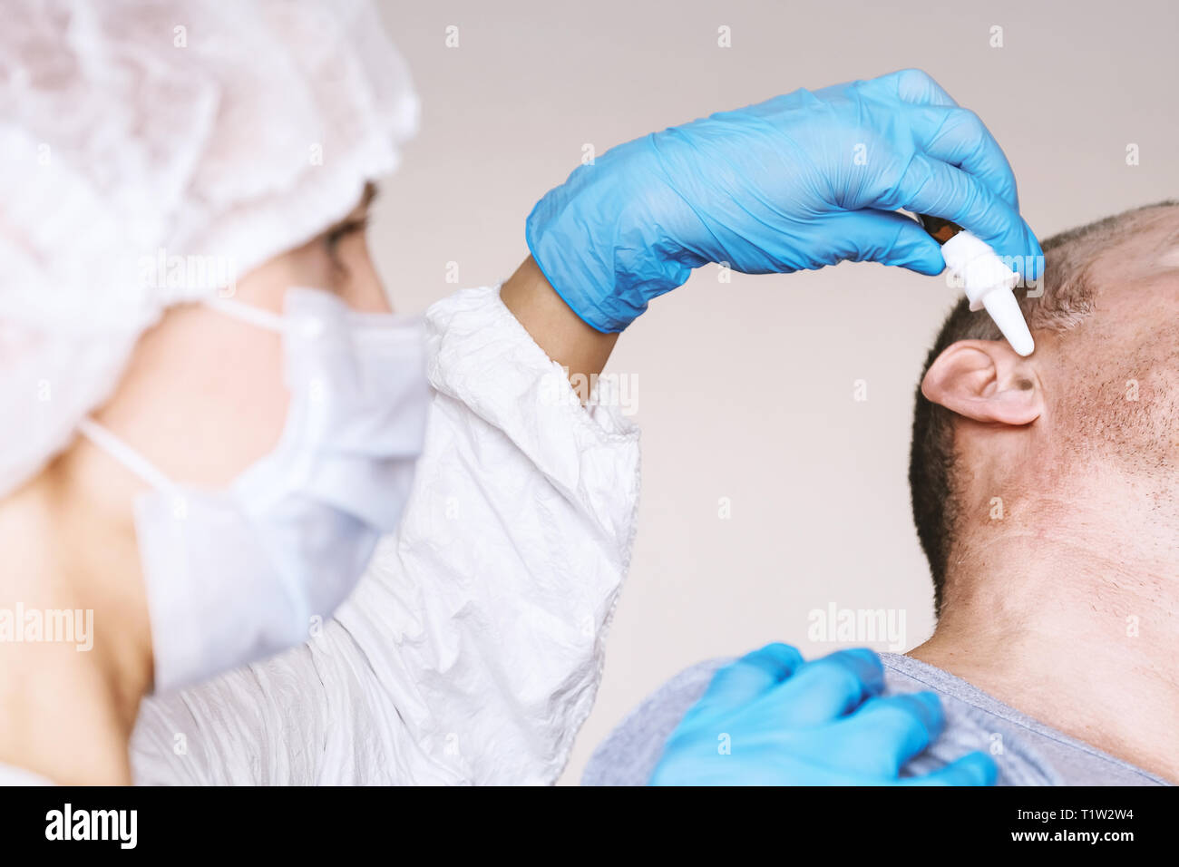 Doctor Otolaryngologist treats the otitis media patient. Buries the ear drops in the ear hole. On the face of a protective mask. Protective suit - Stock Image