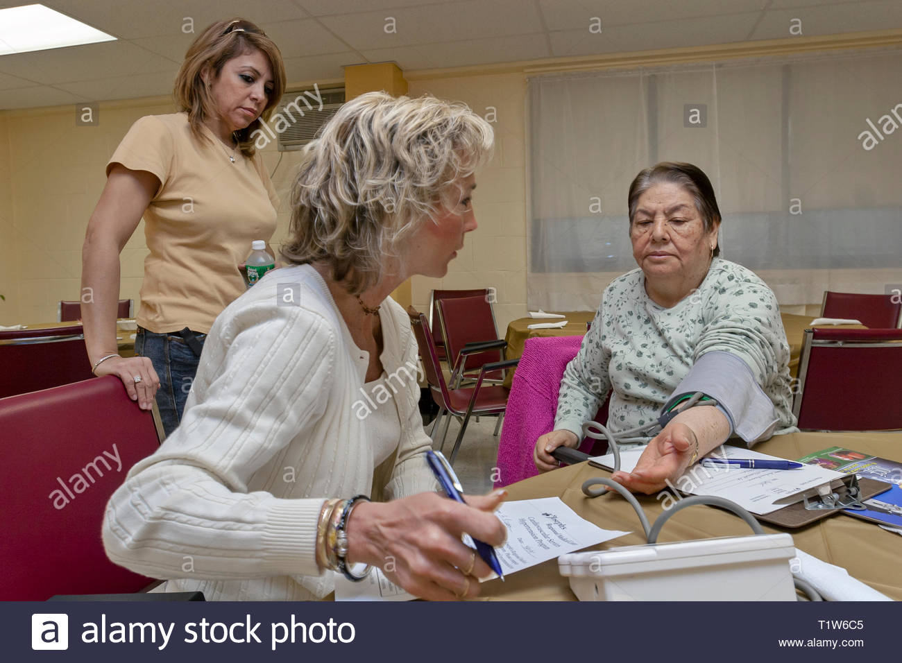 A female nurse takes the blood pressure of a senior woman in a community outreach program. - Stock Image