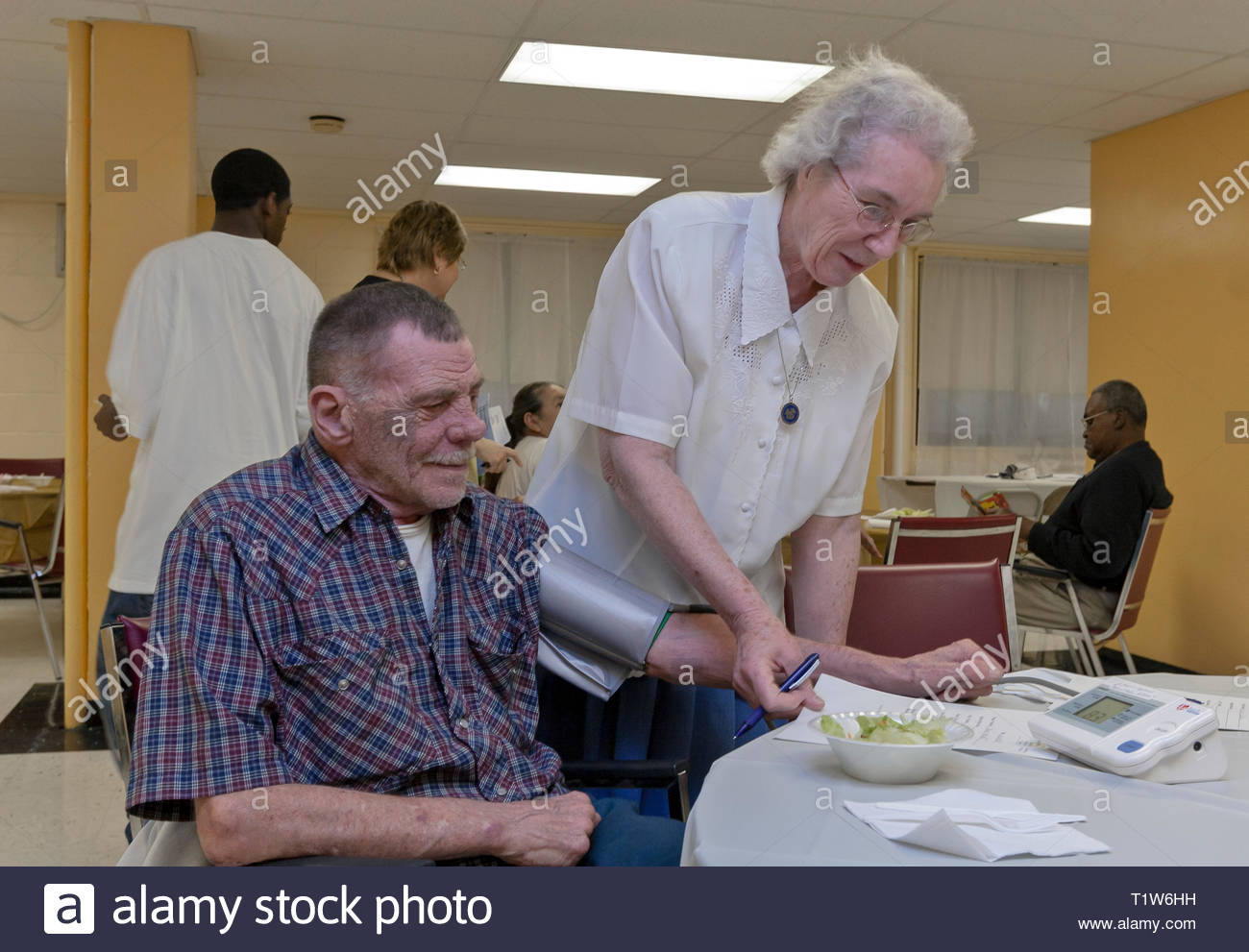 A female nurse takes the blood pressure of a senior man in a community outreach program. - Stock Image