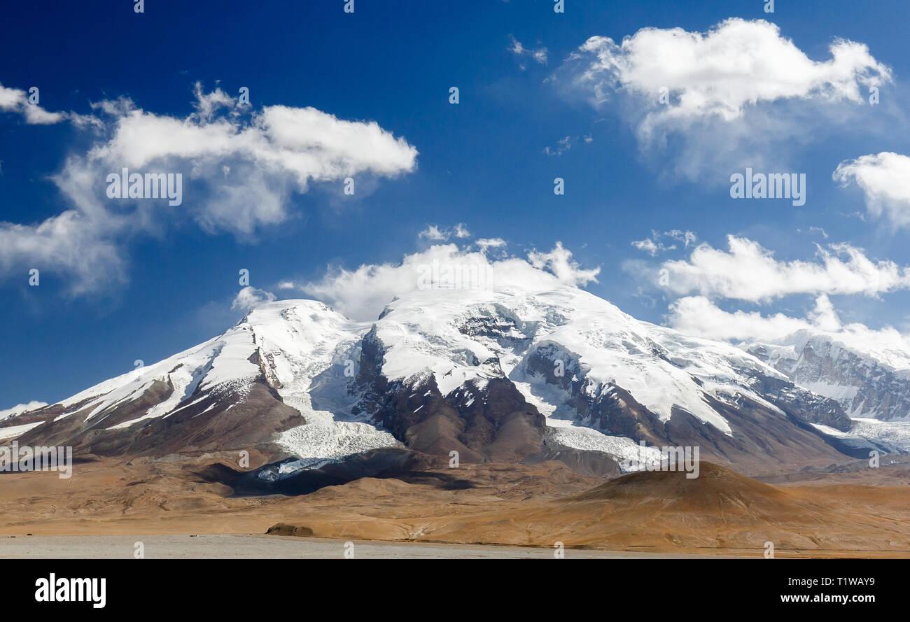 Muztagata Mountain with blue sky and clouds (Karakorum Highway, Xinjiang Province, China) - Stock Image