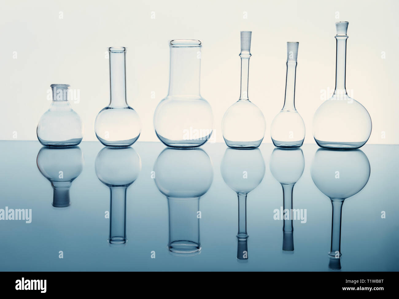 many of the beakers are in a row in the backlight, the reflection, the blue background Stock Photo