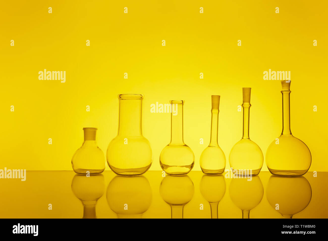 many of the beakers are in a row in the backlight, the reflection, the yellow background Stock Photo