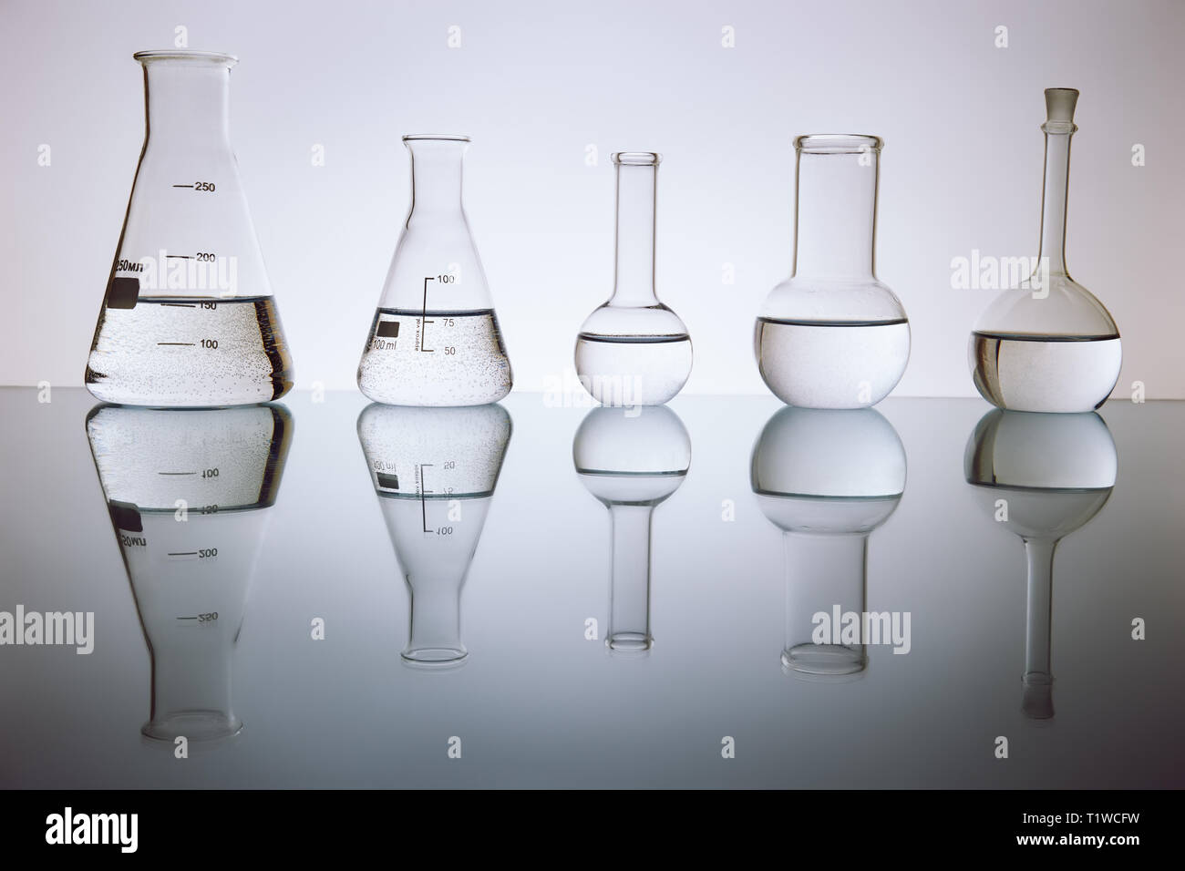 many of the beakers are in a row in the backlight, the reflection, the blue background. with liquid, Stock Photo
