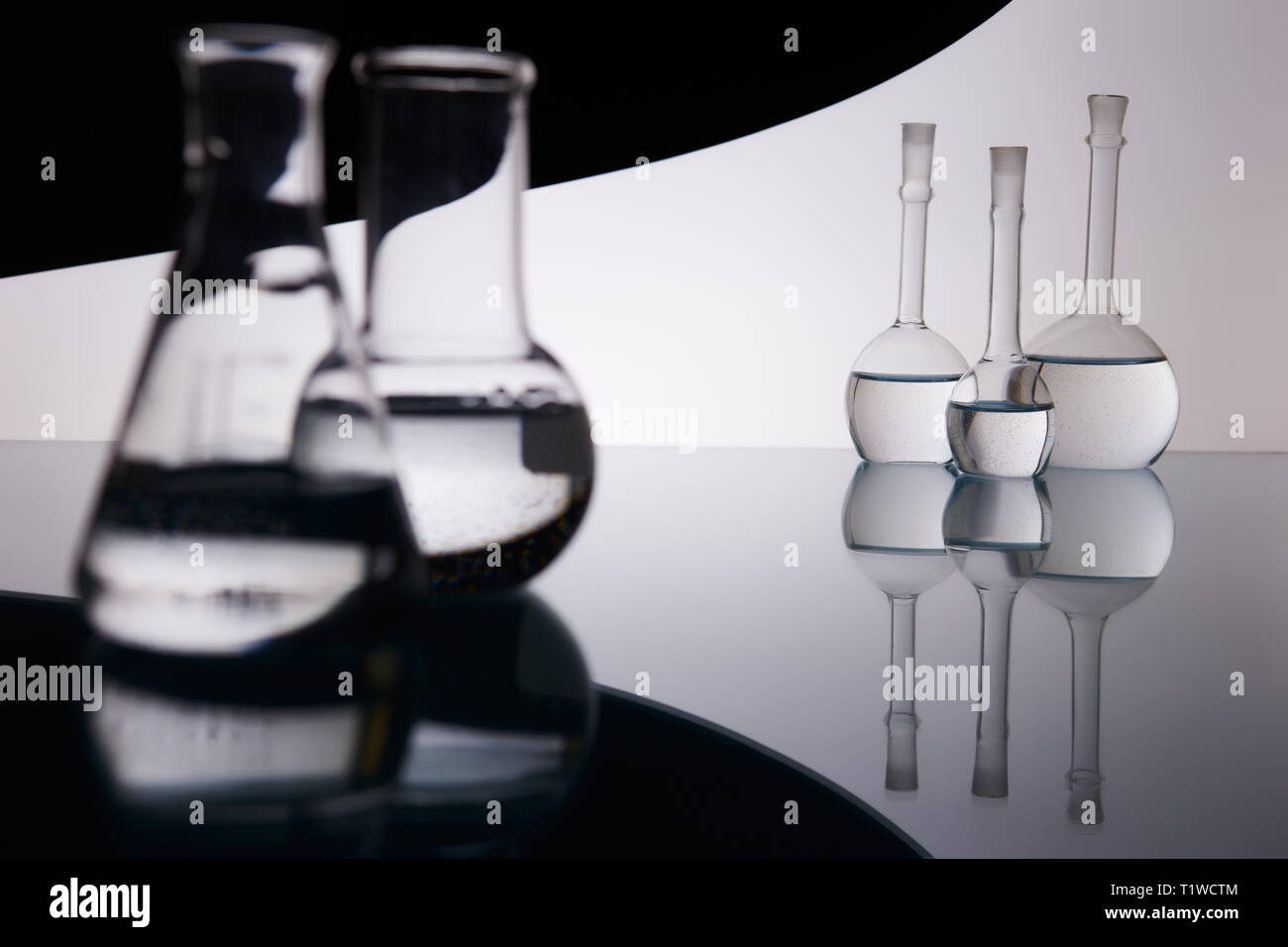 many beakers are in row, with liquid, in backlight, reflection, blue background Stock Photo