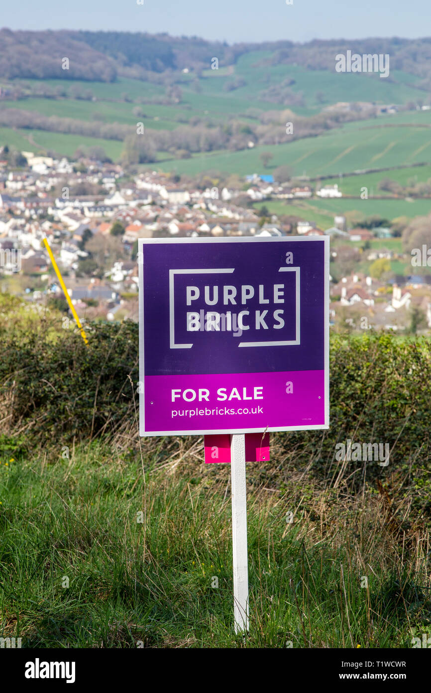 Purple Bricks house for sale sign in open countryside above the village of Sidford, nr Sidmouth, Devon, UK Stock Photo