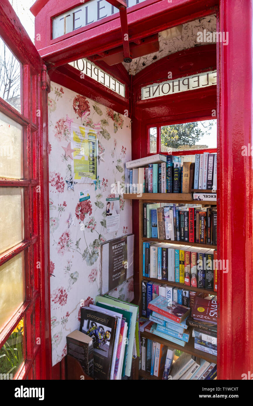 Old GPO telephone box used as a free book store in Fortescue, Sidmouth, Devon, UK. - Stock Image