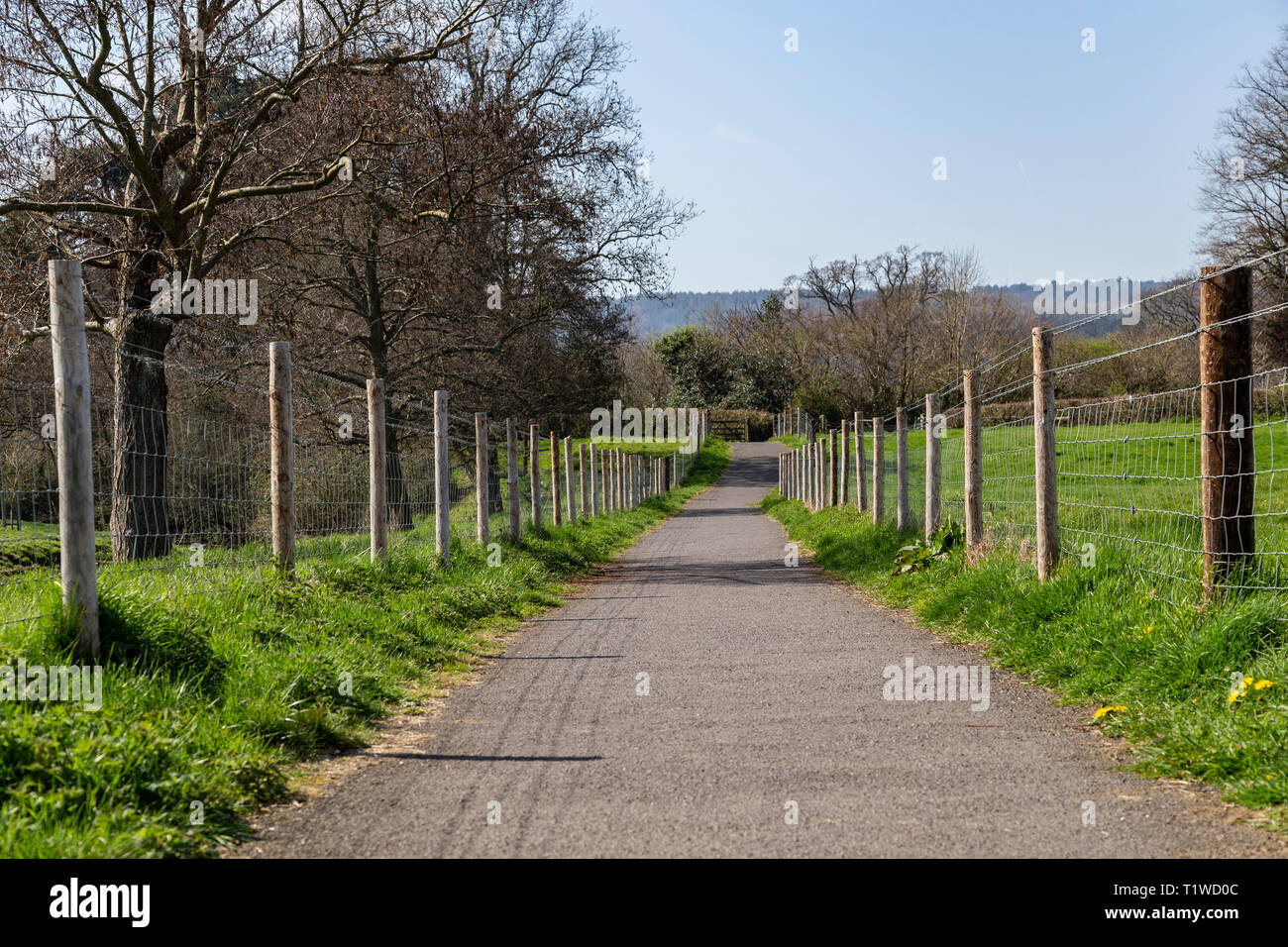 A long tarmac footpath with tall fence posts to both sides. Stock Photo