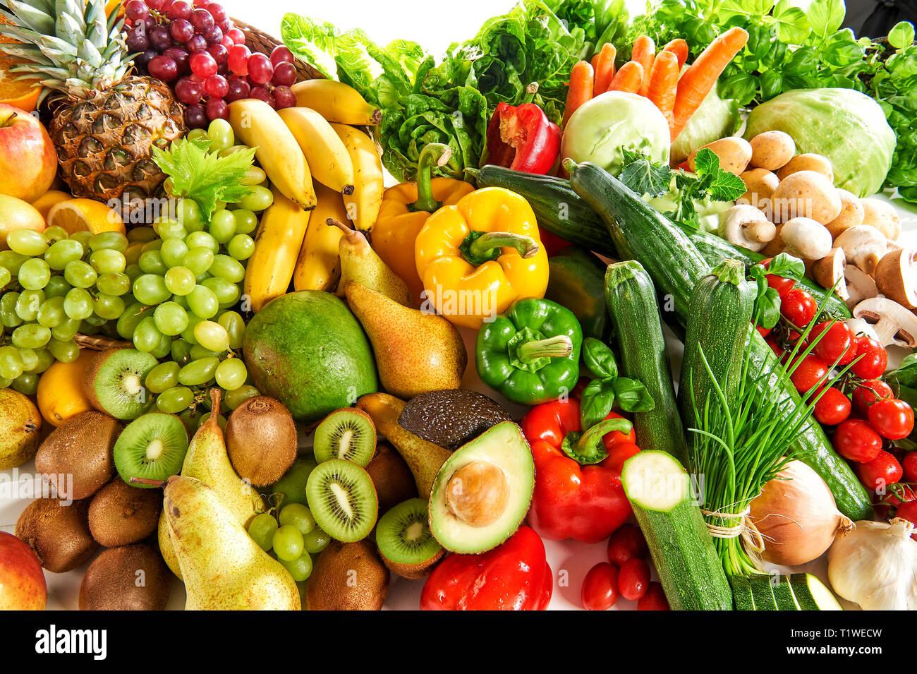 Verschiedene Obst- und Gemuesesorten liegen aufgetuermt. - Stock Image