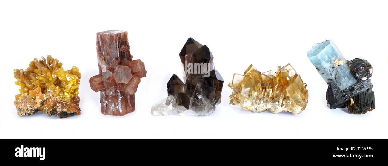 A row of three crystal clusters, Mimetite, Aragonite, Smoky Quartz, Barite (Baryte) and Tourmaline, isolated on a white background. - Stock Image