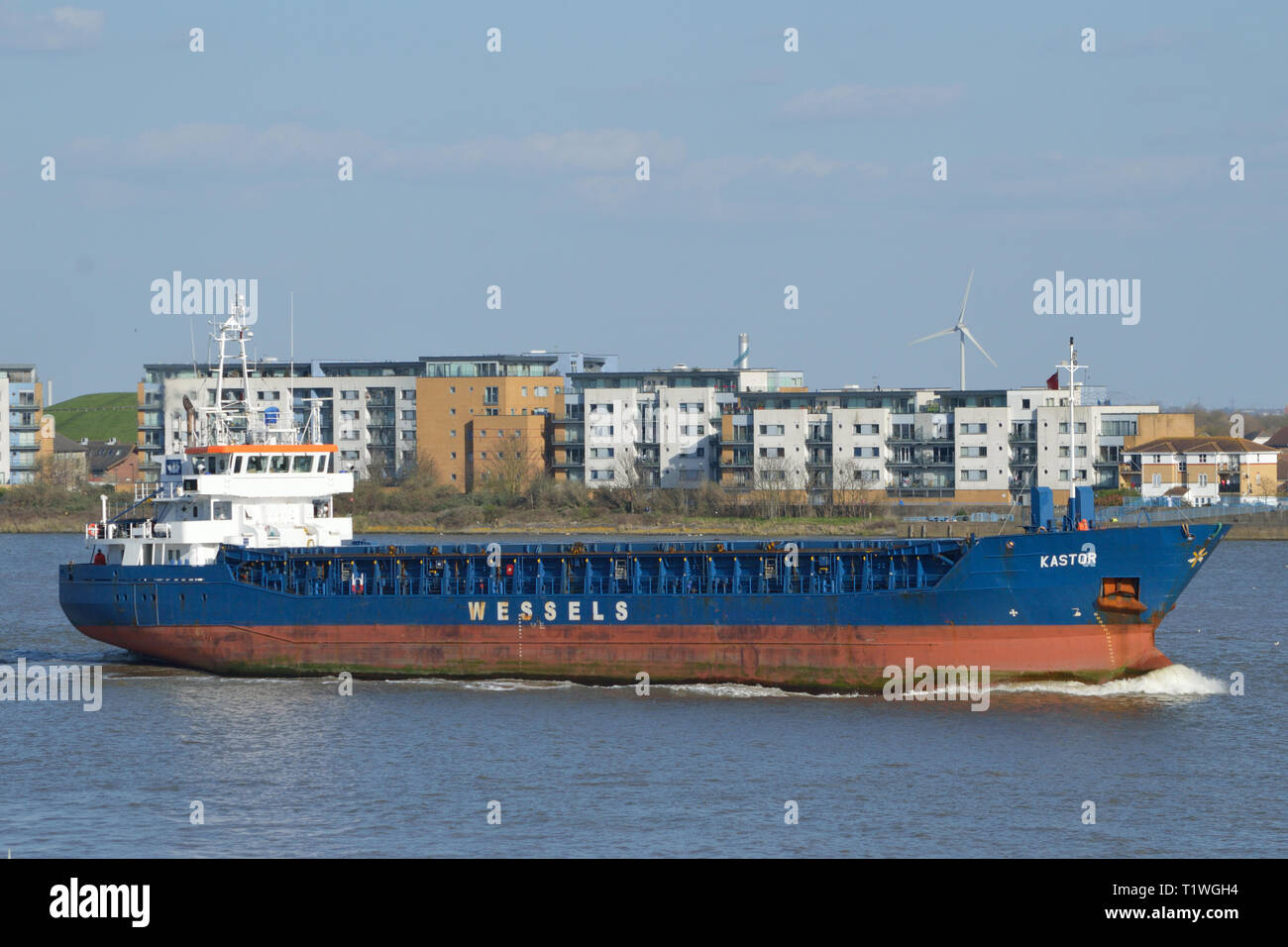 General cargo ship Kastor heads up the River Thames to collect a cargo from London - Stock Image
