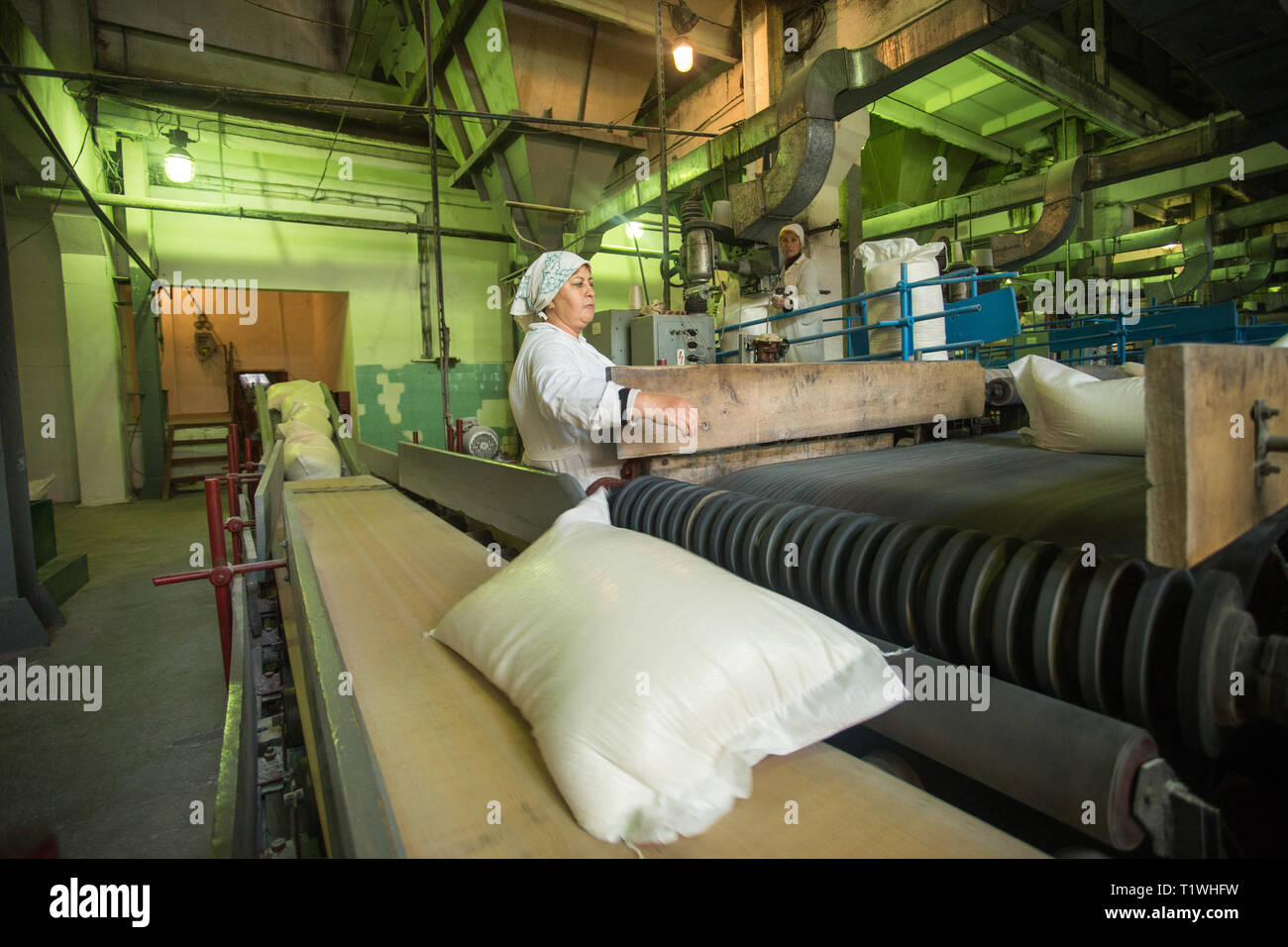 14 october 2014.Ukraine.Kyiv. The woman of average years in a white dressing gown works on a conveyor at factory of times of the Soviet, manual skills Stock Photo